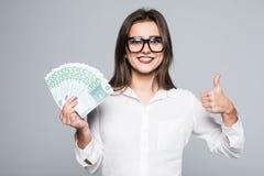 Ritratto di una ragazza allegra che copre il suo occhio di euro fatture e che mostra pollice su isolato su un fondo bianco Immagini Stock Libere da Diritti