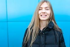 Ritratto di una ragazza allegra e sorridente su fondo blu, con il posto isolato per testo fotografia stock