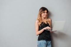 Ritratto di una ragazza allegra felice che per mezzo del computer portatile Fotografia Stock