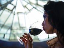 Ritratto di una ragazza attraente con le belle labbra che beve il vino rosso da un vetro immagine stock libera da diritti