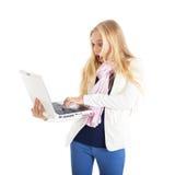 Ritratto di una ragazza bionda con un computer portatile bianco. Fronte sorprendente. Fotografia Stock