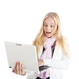 Ritratto di una ragazza bionda con un computer portatile bianco. Fronte sorprendente. Immagine Stock