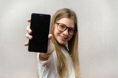 Ritratto di una ragazza bionda con uno smartphone in sua mano Tecnologia astuta Collegamento mobile Apps dello smartphone dei bam immagini stock libere da diritti