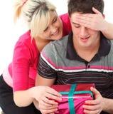 Ritratto di una ragazza che dà al suo ragazzo un regalo Immagine Stock
