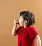 Ritratto di una ragazza che per mezzo dell'inalatore di asma Immagine Stock