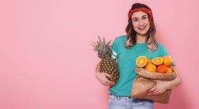 Ritratto di una ragazza con una frutta su un fondo rosa fotografia stock libera da diritti