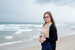Ritratto di una ragazza con i vetri che posano sulla spiaggia un giorno nuvoloso fotografia stock libera da diritti
