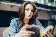 Ritratto di una ragazza con un libro aperto mentre studiando in un caffè Immagini Stock Libere da Diritti