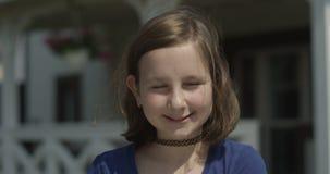 Ritratto di una ragazza del bambino con il girocollo che esamina la macchina fotografica e che sorride all'aperto su Sunny Day al archivi video