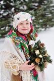 Ritratto di una ragazza del bambino in un foulard nello stile di Urs sui precedenti di neve e della foresta fotografia stock libera da diritti