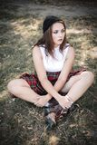 Ritratto di una ragazza dell'età dello studente che si siede sull'erba Il concetto degli adolescenti difficili, cattivi studenti  fotografie stock libere da diritti