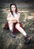 Ritratto di una ragazza dell'età dello studente che si siede sull'erba Il concetto degli adolescenti difficili, cattivi studenti  fotografia stock libera da diritti