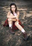 Ritratto di una ragazza dell'età dello studente che si siede sull'erba L'annata ha tonificato la foto immagine stock