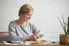 Ritratto di una ragazza dello studente allo scrittorio con il telefono Immagine Stock