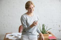 Ritratto di una ragazza dello studente che sta vicino allo scrittorio con un telefono in sua mano Fotografie Stock