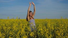 Ritratto di una ragazza dolce in un'accoglienza d'ondeggiamento delle mani del campo giallo archivi video