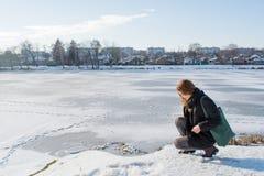 Ritratto di una ragazza europea dei giovani bei capelli rossi che si siede vicino al fiume e che guarda giù Fotografia Stock