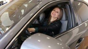 Ritratto di una ragazza felice che conduce una nuova automobile in un concessionario auto stock footage