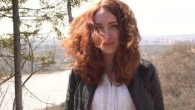Ritratto di una ragazza felice della testarossa con capelli lunghi che esaminano macchina fotografica mentre stando all'aperto video d archivio
