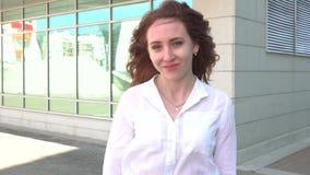 Ritratto di una ragazza felice della testarossa con capelli lunghi che esaminano macchina fotografica mentre stando all'aperto archivi video
