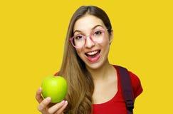 Ritratto di una ragazza felice sorridente del nerd con i vetri e della mela verde in sua mano isolata sopra fondo giallo immagine stock libera da diritti