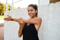 Ritratto di una ragazza di forma fisica dello smilng che allunga le sue mani Immagine Stock Libera da Diritti