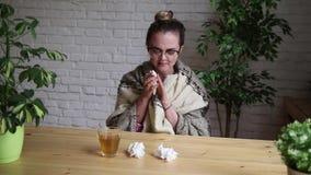 Ritratto di una ragazza frustrata che soffia il suo naso in un fazzoletto mentre lavorando con un computer portatile Il concetto  stock footage
