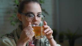 Ritratto di una ragazza frustrata che soffia il suo naso in un fazzoletto mentre lavorando con un computer portatile Il concetto  video d archivio