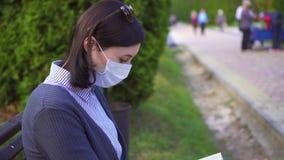 Ritratto di una ragazza in una maschera medica protettiva sul suo fronte e con un libro su un banco al tramonto archivi video