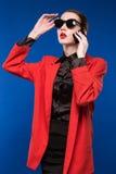 Ritratto di una ragazza in occhiali da sole e con un telefono in sua mano Immagini Stock Libere da Diritti