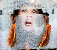 Ritratto di una ragazza per una finestra gelida Fotografia Stock Libera da Diritti