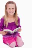Ritratto di una ragazza sorridente che legge un libro Immagini Stock Libere da Diritti