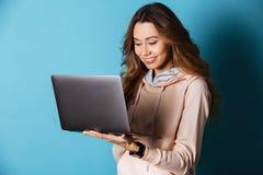 Ritratto di una ragazza sorridente che per mezzo del computer portatile Immagine Stock