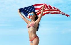 Ritratto di una ragazza sorridente con la bandiera americana Immagini Stock