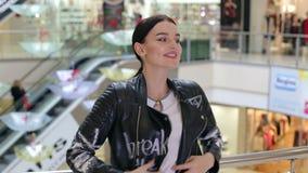 Ritratto di una ragazza sorridente felice nel centro commerciale sui precedenti della scala mobile archivi video
