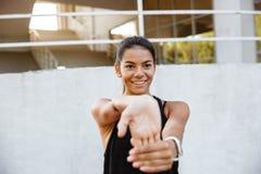 Ritratto di una ragazza sorridente di forma fisica che allunga le sue mani Fotografia Stock