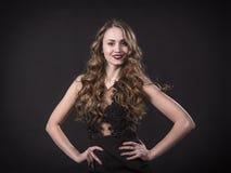 Ritratto di una ragazza sorridente in un vestito dal pizzo su un fondo nero fotografia stock
