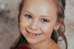 Ritratto di una ragazza sorridente in un vestito rosso e con una bella acconciatura Colpo dello studio fotografia stock