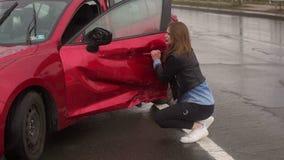 Ritratto di una ragazza spaventata vicino alla sua automobile rotta dopo un incidente su una strada bagnata archivi video