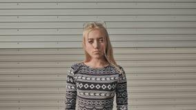 Ritratto di una ragazza teenager seria su un fondo a strisce grigio stock footage