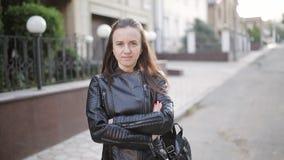 Ritratto di una ragazza in un bomber con uno zaino che sta sulla via nei precedenti della sua nuova casa archivi video