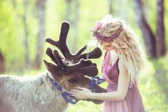 Ritratto di una ragazza in un vestito leggiadramente accanto ad una renna Immagine Stock