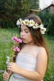 Ritratto di una ragazza in una corona delle camomille su lei capa, che sta odorando un fiore Fotografia Stock Libera da Diritti