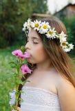 Ritratto di una ragazza in una corona delle camomille su lei capa, che sta odorando un fiore Fotografia Stock