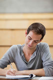 Ritratto di una scrittura dell'allievo maschio su un blocchetto per appunti Fotografie Stock