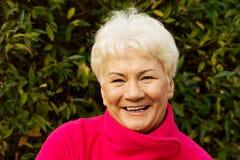 Ritratto di una signora anziana allegra sopra fondo verde. Fotografie Stock