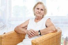 Ritratto di una signora anziana che si siede in una sedia Immagine Stock Libera da Diritti