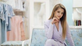 Ritratto di una signora attraente di affari che si siede sullo strato e che esamina la macchina fotografica in un deposito militi stock footage