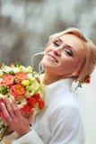 Ritratto di una sposa sorridente felice, tenendo i fiori e guardando a Fotografia Stock