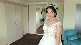 Ritratto di una sposa tenera sveglia in un vestito da sposa bianco archivi video